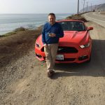 We hired a Ford Mustang to travel to style while stateside in California. Here, I pulled over to make a call with the North Pacific Ocean in the background.